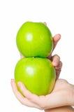 Nas mãos bonitas uma maçã verde, isolada no fundo branco Foto de Stock