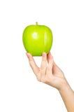 Nas mãos bonitas uma maçã verde, isolada no fundo branco Fotografia de Stock