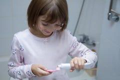 Nas mãos da escova de dentes e do dentífrico da criança foto de stock