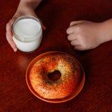 Nas mãos de um vidro do leite fresco e de um bagel na tabela Imagens de Stock