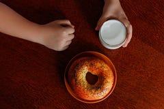 Nas mãos de um vidro do leite fresco e de um bagel na tabela Fotografia de Stock Royalty Free
