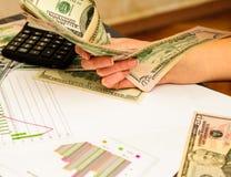 Nas mãos do dólar americano, fundo com a carta t da calculadora Tudo para o nível financeiro imagens de stock
