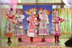 Nas meninas bonitas da fase em trajes nacionais do russo, sundresses dos vestidos com bordado vibrante - grupo da música folk a r Foto de Stock Royalty Free