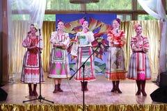 Nas meninas bonitas da fase em trajes nacionais do russo, sundresses dos vestidos com bordado vibrante - grupo da música folk a r Fotos de Stock