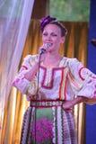 Nas meninas bonitas da fase em trajes nacionais do russo, sundresses dos vestidos com bordado vibrante - grupo da música folk a r Fotografia de Stock