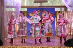 Nas meninas bonitas da fase em trajes nacionais do russo, sundresses dos vestidos com bordado vibrante - grupo da música folk a r Fotos de Stock Royalty Free
