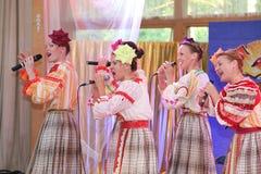 Nas meninas bonitas da fase em trajes nacionais do russo, sundresses dos vestidos com bordado vibrante - grupo da música folk a r Foto de Stock