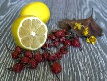 Nas mentiras da tabela um limão do corte, ao lado do fruto do rosehip fotos de stock