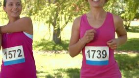 Nas mulheres de sorriso do formato de alta qualidade que correm para a conscientização do câncer da mama vídeos de arquivo