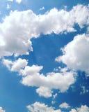 Nas nuvens de cúmulo brancas solares do céu azul sob a forma do coração fotografia de stock