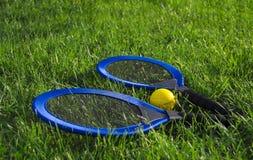 Nas raquetes azuis da mentira dois do gramado da grama verde e em uma bola de tênis amarela imagens de stock