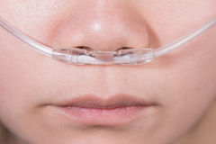Nasal cannula for oxygen delivery on a woman patient Stock Photos