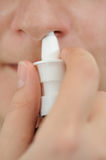 The nasal spray. The woman splashes in a nose a spray for a nose Stock Image