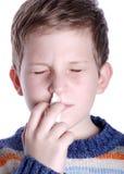 Nasal spray. Nine year old boy spraying nasal spray nostril Royalty Free Stock Photo