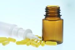 Nasal spray and capsules. Nasal spray and yellow medical capsules Royalty Free Stock Photography