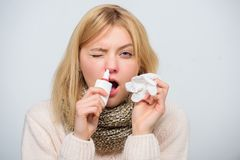 Nasal spray runny nose remedy. Girl sick person hold nasal drops and tissue. Home treatment. Nasal drops plastic bottle. Effective nasal spray. Runny nose and royalty free stock photo