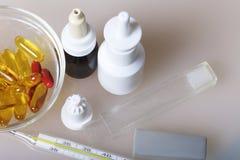 Nasala droppar, sprej och preventivpillerar i en glass behållare, ställning på yttersidan Närliggande är en termometer för att mä Arkivbilder