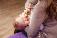 Nasale Tropfen des Frauenbratenfetts zu einem Kind stockfoto