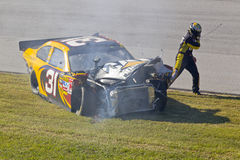 NASCAR:  Oct 31 AMP Energy Juice 500. TALLADEGA, AL - OCT 31, 2010:  Jeff Burton exits out of his crashed CAT Chevrolet during the AMP Energy Juice 500 race at Stock Image