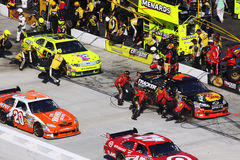 NASCAR - Pit Road Is Busy!. Other cars come onto to pit road during a caution while the pit crews for Martin Trux Jr and and Paul Menard teams begin servicing royalty free stock photo