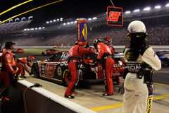 NASCAR's Watchful Eye. Elliot Sadler's pit crew races to complete their pit stop as fast as possible as a NASCAR official watches closely during 2006 Bank of stock images