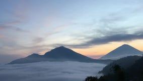 Nascer do sol acima do lago Batur coberto com as nuvens - vistas da parte superior da montagem Batur em Bali, Indonésia filme