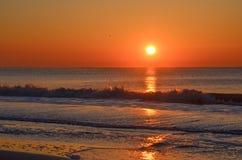 Nascer do sol alaranjado profundo ao longo da linha costeira litoral atlântica acima das ondas deixando de funcionar fotos de stock royalty free