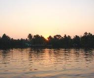 Nascer do sol atrás das árvores sobre o canal da maré, Kerala, Índia Imagem de Stock Royalty Free