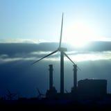 Nascer do sol atrás do central elétrica e das turbinas eólicas bondes Imagens de Stock Royalty Free