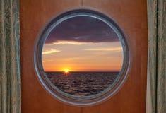 Nascer do sol através da vigia Fotos de Stock