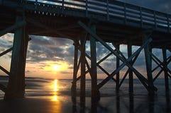 Nascer do sol através das colunas do cais Fotos de Stock