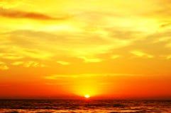 Nascer do sol através do oceano Imagens de Stock
