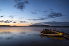 Nascer do sol bonito da paisagem sobre o lago imóvel com os barcos no molhe Imagem de Stock