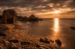 Nascer do sol bonito do oceano - o mar calmo e os pedregulhos apedrejam o litoral Imagem de Stock Royalty Free