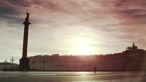 Nascer do sol bonito do verão sobre o quadrado vazio do palácio em St Petersburg O turista só passa o quadrado do throuth filme