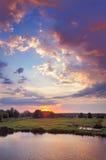 Nascer do sol bonito e nuvens românticas no céu. Imagem de Stock