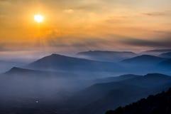 Nascer do sol bonito, névoa e montanhas Foto de Stock Royalty Free