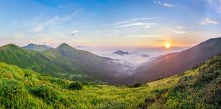 Nascer do sol bonito nas montanhas com névoa branca abaixo do panorama fotografia de stock royalty free