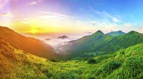 Nascer do sol bonito nas montanhas com névoa branca abaixo do panorama fotografia de stock