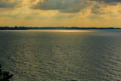 Nascer do sol bonito sobre o mar na manhã no dia nebuloso que o sol irradia a ruptura através das nuvens Sun que irradia-se atrav Imagens de Stock Royalty Free