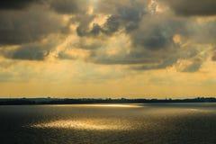 Nascer do sol bonito sobre o mar na manhã no dia nebuloso que o sol irradia a ruptura através das nuvens Sun que irradia-se atrav Foto de Stock