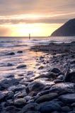 Nascer do sol bonito sobre o oceano com penhascos e rochas Foto de Stock