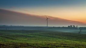 Nascer do sol bonito sobre um campo com um moinho de vento no outono vídeos de arquivo