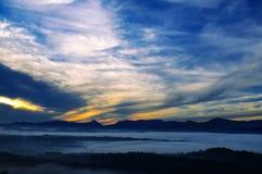 Nascer do sol brilhante, a névoa em um vale da montanha e picos de montanha Foto de Stock