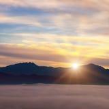 Nascer do sol brilhante, a névoa em um vale da montanha e picos de montanha Imagens de Stock Royalty Free