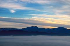Nascer do sol brilhante, a névoa em um vale da montanha e picos de montanha Fotografia de Stock Royalty Free