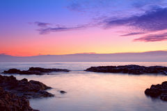 Nascer do sol colorido na costa rochosa foto de stock