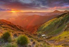 Nascer do sol colorido surpreendente nas montanhas com raios de sol coloridos e f Foto de Stock Royalty Free