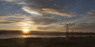 Nascer do sol com céu azul e névoa na água Fotos de Stock