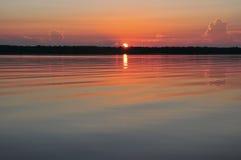 Nascer do sol com reflexão na água calma Imagens de Stock Royalty Free